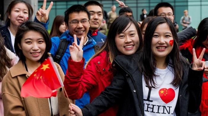 китайские студенты держат флаг Китая